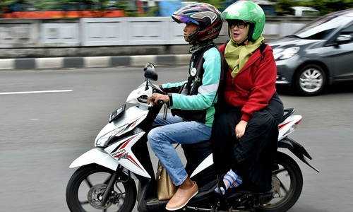 A GrabBike rider transports a passenger in Jakarta on February 2, 2017. Southeast Asian ride-hailing firm Grab on Thursday unveiled a plan to invest $700 million in Indonesia over the next four years, as transport app competition in the country accelerates. / AFP / Bay ISMOYO        (Photo credit should read BAY ISMOYO/AFP/Getty Images)